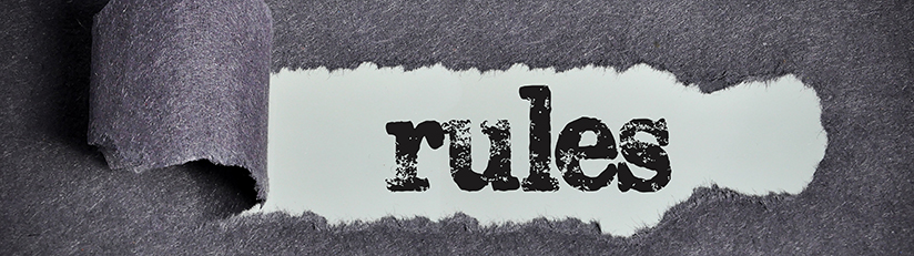 photo of torn paper revealing the word rules